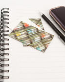Pen and mobile phone and cards on notepad — Stock Photo