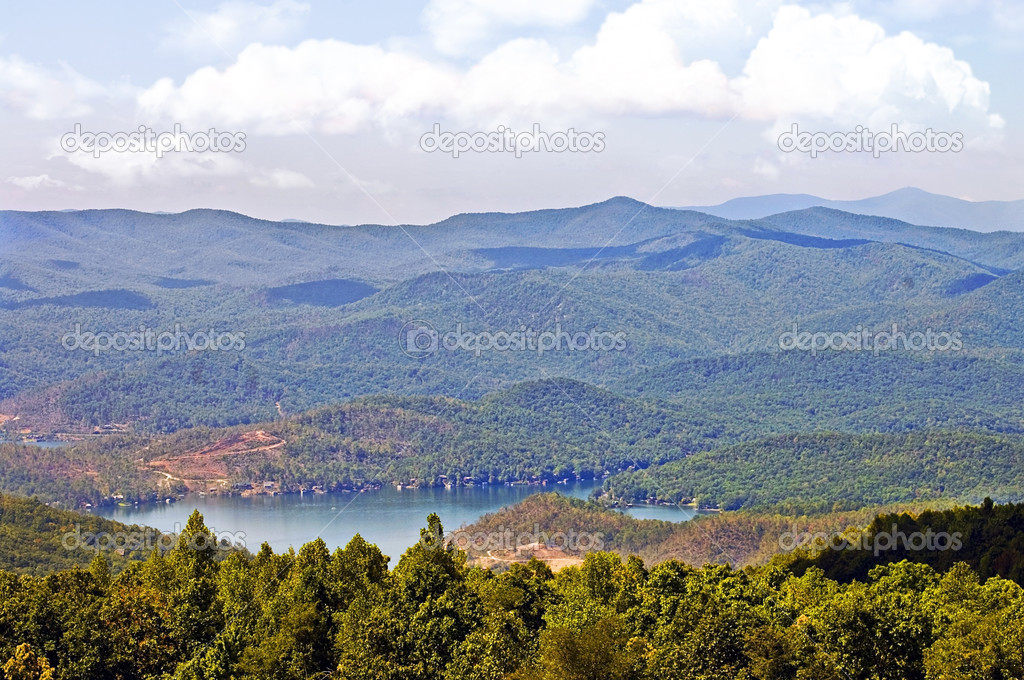 A long range mountain view with lake.  The areas of clearing are where a tornado did damage. — Stock Photo #6823761