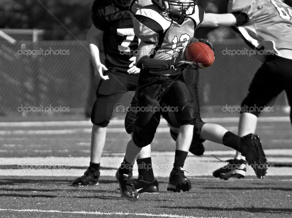 A young boy carrying the ball during a youth league football game, black and white. — Stock Photo #7150836
