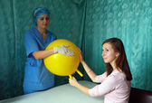 Physician and patient in their hands massaging yellow inflatable ball — Stock Photo