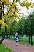 La colegiala caminando por el parque otoño avenue — Foto de Stock