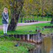 Stock Photo: Schoolgirl of feeding ducks on pond, autumn park
