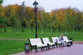 The schoolgirl sitting on a bench in Autumn Park — Stock Photo