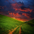Hills and road to red clouds — Stock Photo