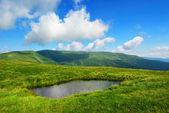 Piccolo lago sul prato e soffici nuvole — Foto Stock