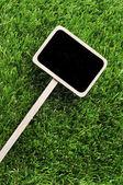 Blank blackboard label on the grass — Stock Photo