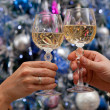 Hands holding glasses of champagne against new year tree — Stock Photo