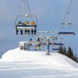 Skiers in chairlift arriving to top of mountain — Stock Photo