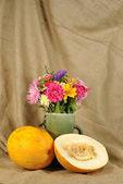 The autumn flowers and orange melon — Stock Photo