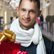 Young handsome man with christmas gifts — Stock Photo