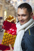 Young adult man with christmas gifts — Stock Photo