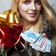 Woman with money and red christmas gift — Stock Photo