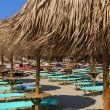 The beach near the blue sea with sun beds and umbrellas — ストック写真