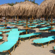 The beach near the blue sea with sun beds and umbrellas — Stock Photo