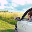 Beautiful woman looking from window of sport car in the field — Stockfoto