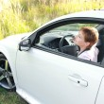 atrakcyjna kobieta poszukuje od sportu biały auto na polu — Zdjęcie stockowe