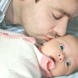 Stock Photo: Macro portrait of handsome father kissing little baby girl
