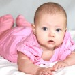 Beautiful baby girl lying and looking in camera — Stock Photo