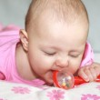Beautiful baby girl in pink clothes playing with red rattle toy — Stock Photo #7728893