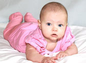 Beautiful baby girl lying and looking in camera — Стоковое фото