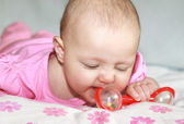 Beautiful baby girl in pink clothes playing with red rattle toy — Stock Photo