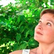 Closeup portrait of beautiful woman looking up on green trees ba — Stock Photo