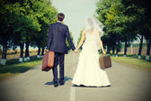 Couple holding suitcases on road — Stock Photo