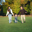 Family Enjoying Walk In autumn Park - Stock Photo
