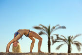 Woman stretching on beach — Stock Photo