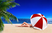 Woman sunbathing on the beach — Stockfoto