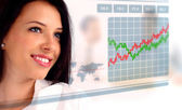 Young woman looking at a stock chart — Stock Photo