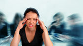 Woman heaving a headache at work — Stock Photo
