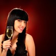 Smiling woman holding a glass of champagne — Stock Photo