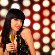 Smiling woman with a glass of champagne — Stock Photo