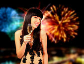 Sexy woman with champagne over fireworks background — Stock Photo