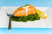 Salmon steak on spinach, decorated with lemon and sauce — Stock Photo