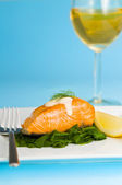 Salmon steak on spinach with a glass of wine — Photo