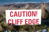 滑悬崖边缘上的红色警告标志 — 图库照片