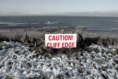 Red caution sign on cliffs slippery edge — Stock Photo