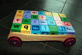 Childrens toy letter building blocks in cart — Stock Photo