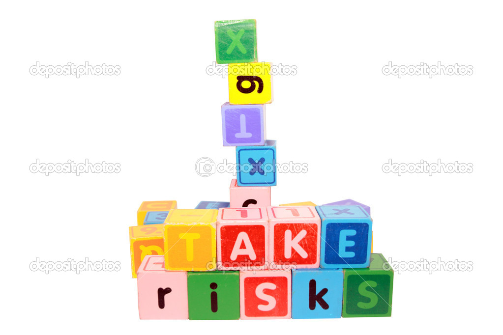 Assorted childrens toy letter building blocks against a white background that spell take risks — Stock Photo #7613992