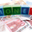 Money in toy play block letters — Stock Photo