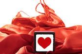 İpek geceliği üzerinde oyuncak aşk kalp — Stok fotoğraf