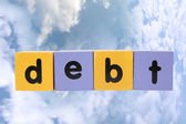 Debt in toy play block letters with clipping path on clouds — Stock Photo