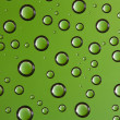 Water drops over green background — Stock Photo