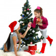 Mother and daughter near a christmas tree with gifts, isolated on a white b — Foto de Stock