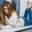 Beautiful long-haired girl, sitting on window-sill — Stock Photo #7571405