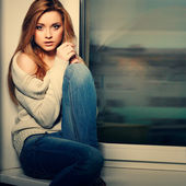 Beautiful long-haired girl, sitting on a window-sill — Stock Photo