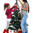 Mother and daughter near a christmas tree with gifts, isolated on a white b — Stock Photo