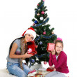 Mother and daughter near a christmas tree with gifts, isolated on a white b — Stock Photo #7828447